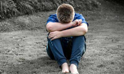 Menino triste sentado no chão